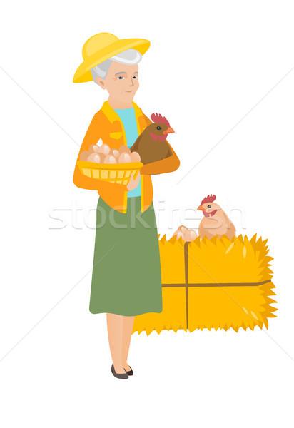 Senior farmer holding chicken and basket of eggs. Stock photo © RAStudio