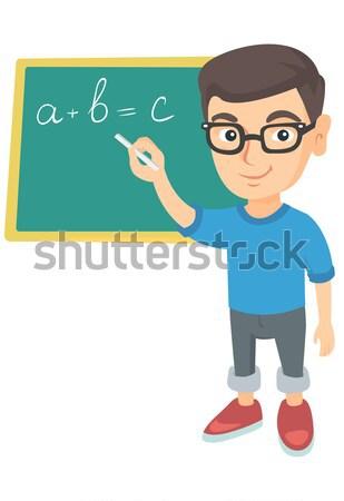 Caucasian schoolboy writing on the blackboard. Stock photo © RAStudio