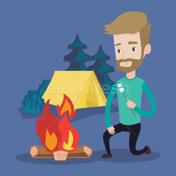 Businessman roasting marshmallow over campfire. Stock photo © RAStudio