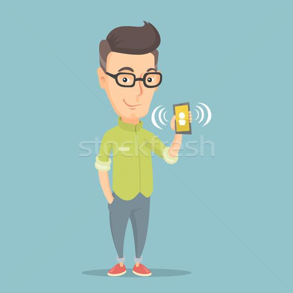 Man holding ringing mobile phone. Stock photo © RAStudio