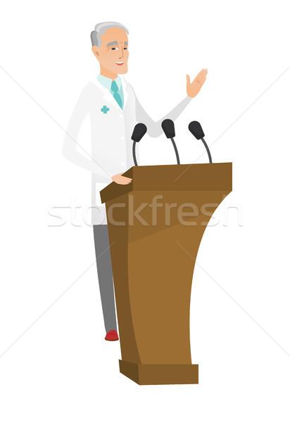 Caucasian doctor giving a speech from tribune. Stock photo © RAStudio