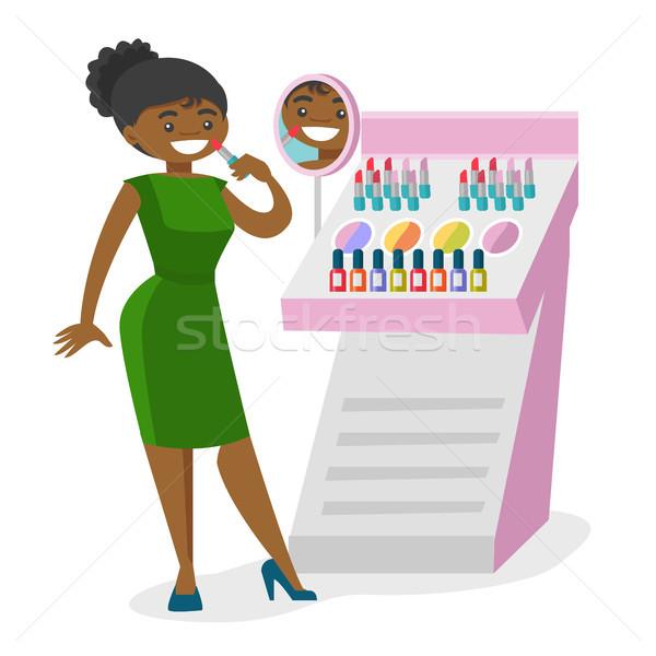 Young african-american woman buying lipstick. Stock photo © RAStudio