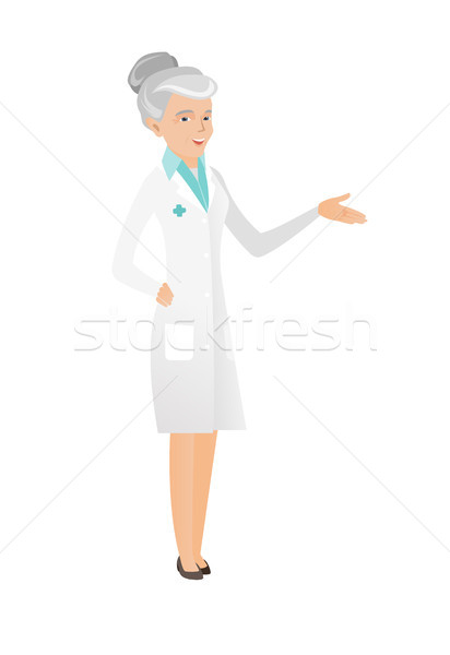 Senior doctor with arm out in a welcoming gesture. Stock photo © RAStudio
