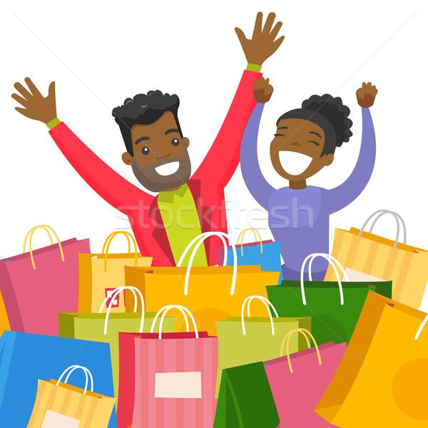 Young african couple sitting among shopping bags. Stock photo © RAStudio