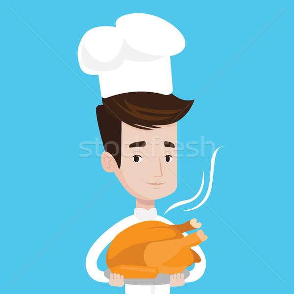 Chief cooker holding roasted chicken. Stock photo © RAStudio