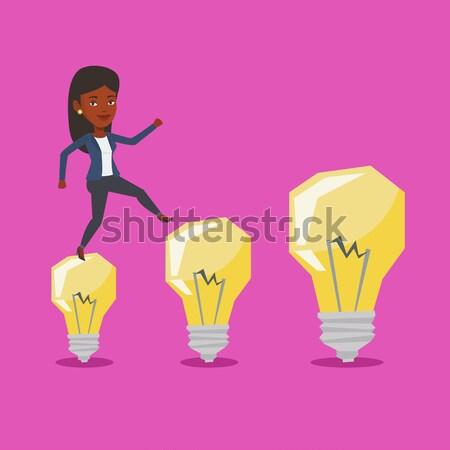 Businessman jumping on idea bulbs. Stock photo © RAStudio