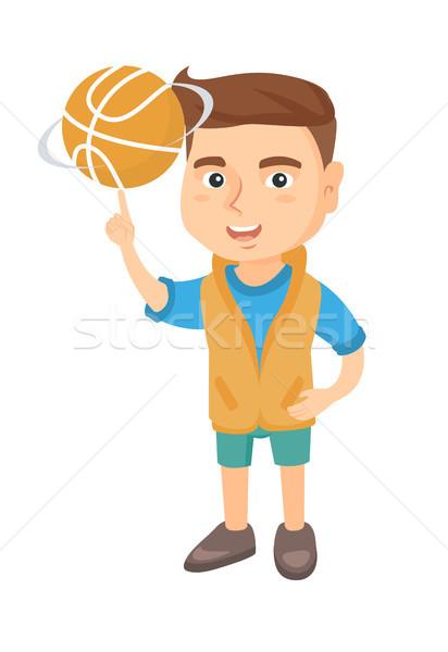 Caucasian boy spinning basketball ball on finger. Stock photo © RAStudio
