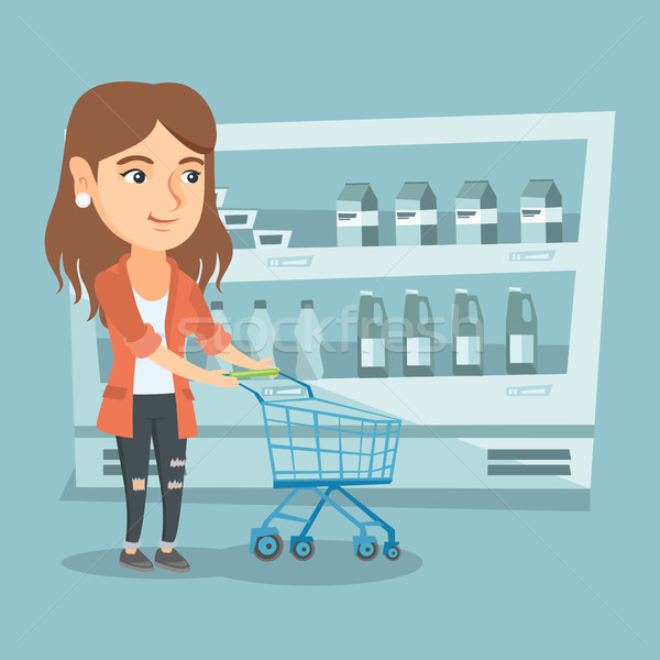 Young caucasian woman with a supermarket trolley. Stock photo © RAStudio