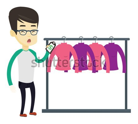 Man shocked by price tag in clothing store. Stock photo © RAStudio