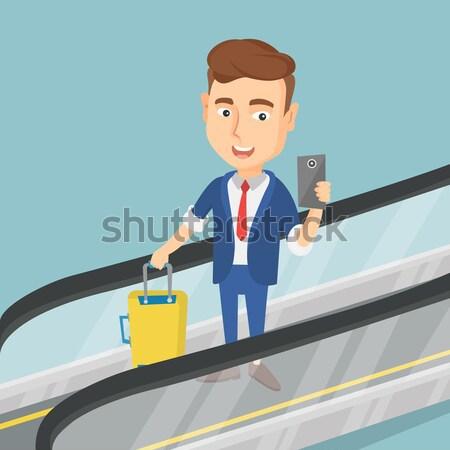 Woman using smartphone on escalator in airport. Stock photo © RAStudio