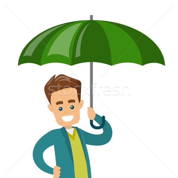 Caucasian insurance agent standing under umbrella. Stock photo © RAStudio
