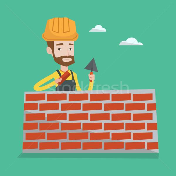 Bricklayer working with spatula and brick. Stock photo © RAStudio
