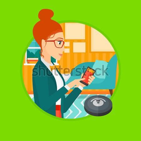Woman controlling vacuum cleaner with smartphone. Stock photo © RAStudio
