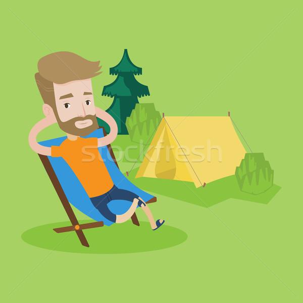 Man sitting in folding chair in the camp. Stock photo © RAStudio