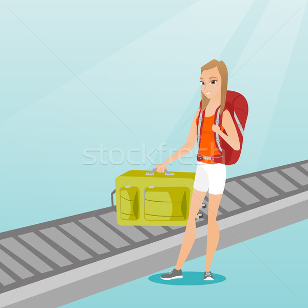 Woman picking up suitcase from conveyor belt. Stock photo © RAStudio