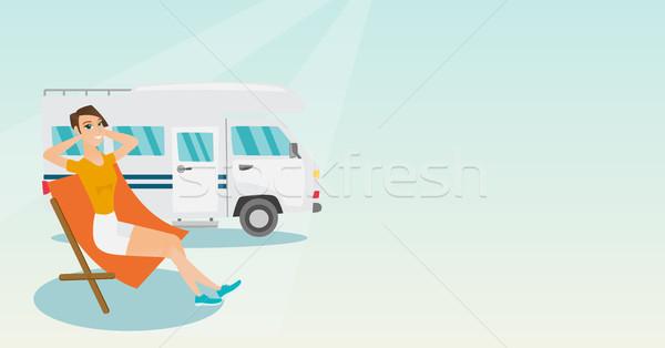 Woman sitting in a chair in front of camper van. Stock photo © RAStudio