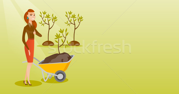 Woman pushing wheelbarrow with plant. Stock photo © RAStudio