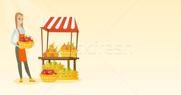 Greengrocer holding box full of apples. Stock photo © RAStudio