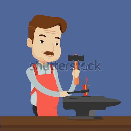 Blacksmith working metal with hammer on the anvil. Stock photo © RAStudio