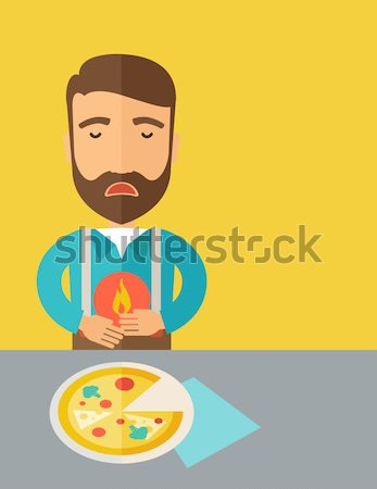 Man has a stomach burn or abdominal pain after he ate pizza. Stock photo © RAStudio