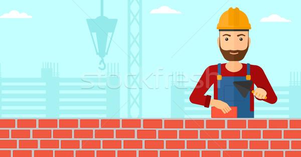 Bricklayer with spatula and brick. Stock photo © RAStudio