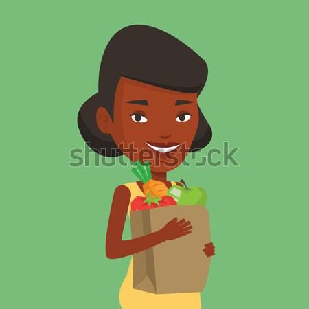 Happy woman holding grocery shopping bag. Stock photo © RAStudio