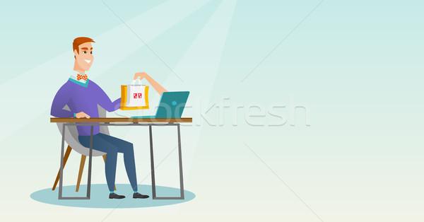 Caucasian man getting shopping bags from a laptop. Stock photo © RAStudio