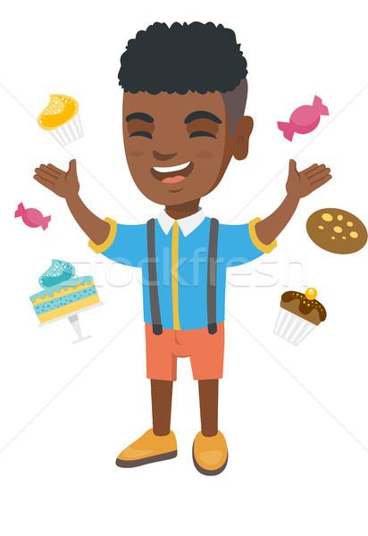 Happy african boy standing among lots of sweets. Stock photo © RAStudio