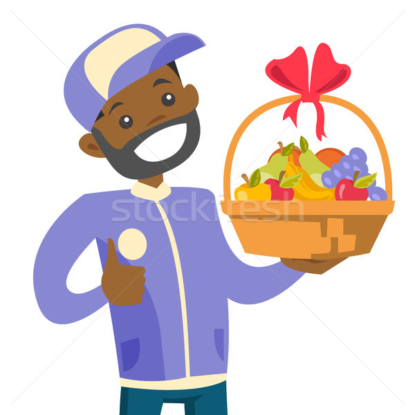 African delivery courier delivering fruit basket. Stock photo © RAStudio