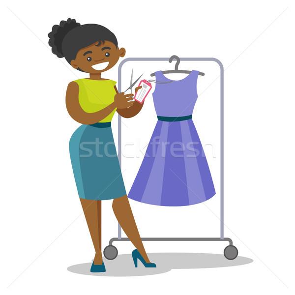African woman cutting price tag off new dress. Stock photo © RAStudio