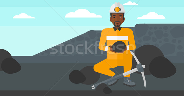 Stock photo: Miner holding coal in hands.