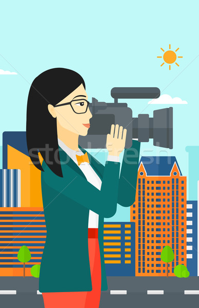 Stock photo: Camerawoman with video camera.