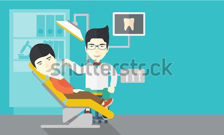 Dentist man examines a patient's teeth in the clinic Stock photo © RAStudio