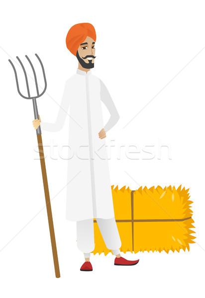 Young hindu farmer holding a pitchfork. Stock photo © RAStudio