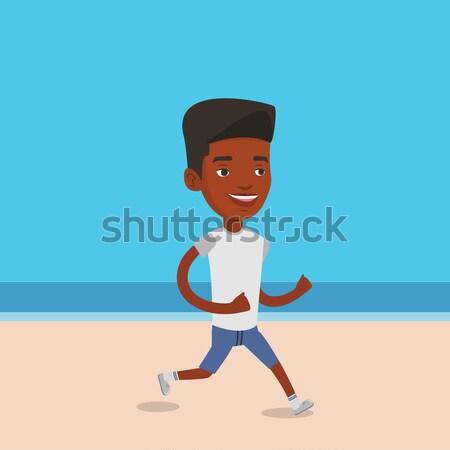 Young sporty man jogging on the beach. Stock photo © RAStudio