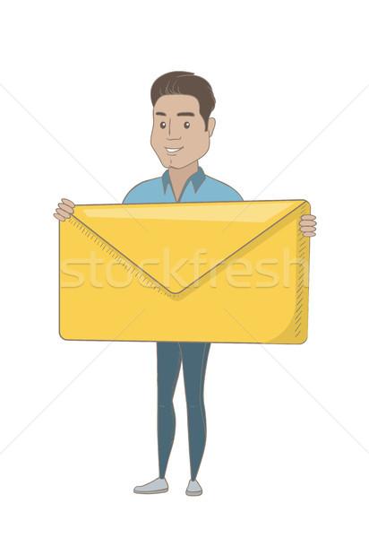 Young hispanic businessman holding big envelope. Stock photo © RAStudio