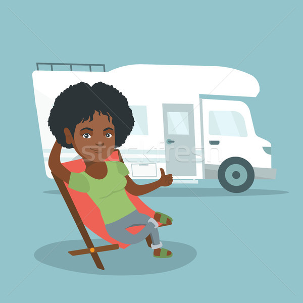 Woman sitting in a chair in front of camper van. Stock photo © RAStudio
