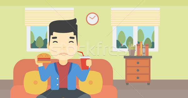 Man eten hamburger asian jonge man vergadering Stockfoto © RAStudio