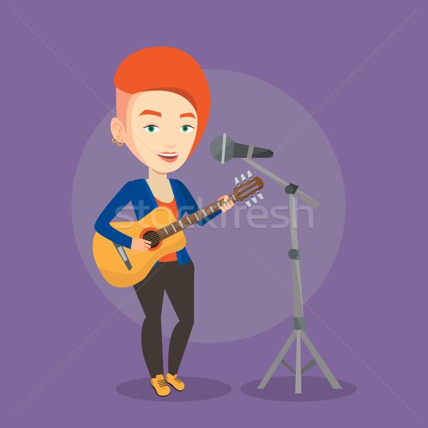 Woman singing in microphone and playing guitar. Stock photo © RAStudio