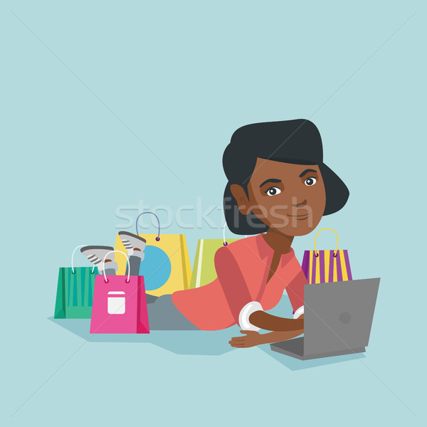 Young african-american woman doing online shopping Stock photo © RAStudio