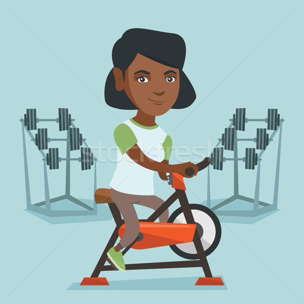 Young african woman riding stationary bicycle. Stock photo © RAStudio