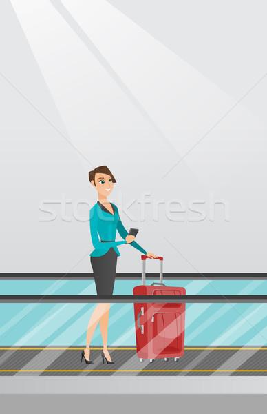 Vrouw smartphone roltrap luchthaven jonge kaukasisch Stockfoto © RAStudio