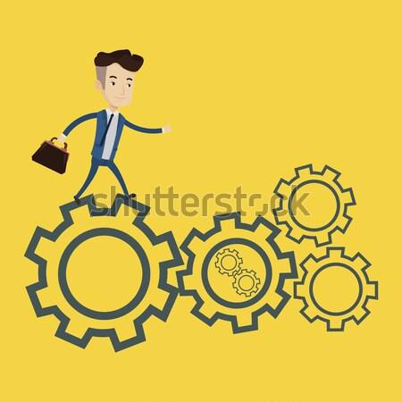 Businessman running on cogwheels. Stock photo © RAStudio