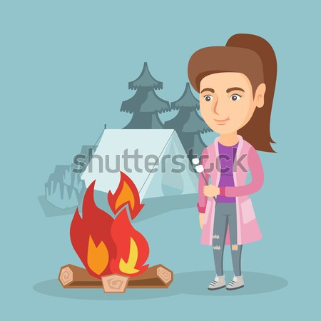 Woman roasting marshmallow over campfire. Stock photo © RAStudio