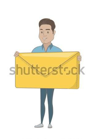 Smiling businessman holding a big envelope. Stock photo © RAStudio