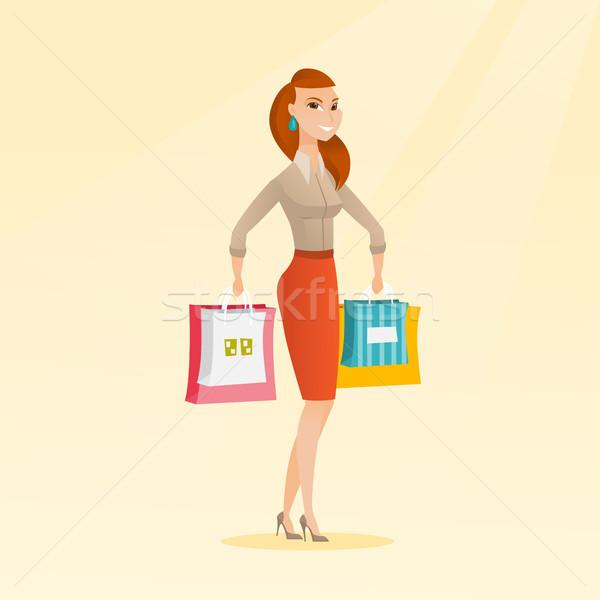 Young happy caucasian woman with shopping bags. Stock photo © RAStudio