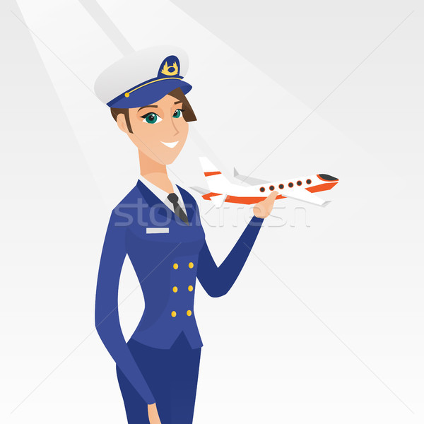 Cheerful airline pilot with the model of airplane. Stock photo © RAStudio