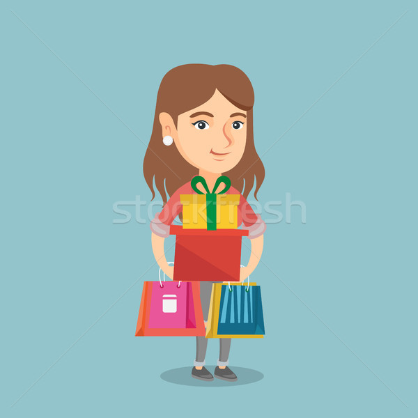 Young woman holding shopping bags and gift boxes. Stock photo © RAStudio