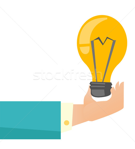 Hand of business person holding bright light bulb. Stock photo © RAStudio