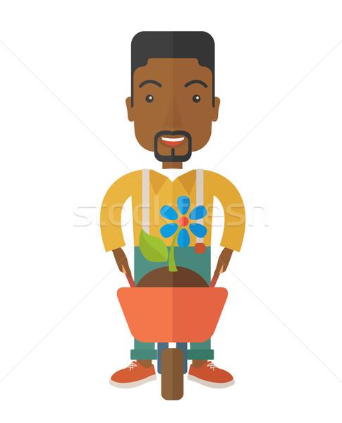 Homme brouette homme noir poussant usine fleur Photo stock © RAStudio